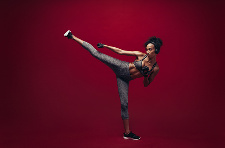 African female fighter practising high kick in studio. Full length shot of fit woman athlete performing a high kick over red background. Martial arts woman exercising taekwondo.