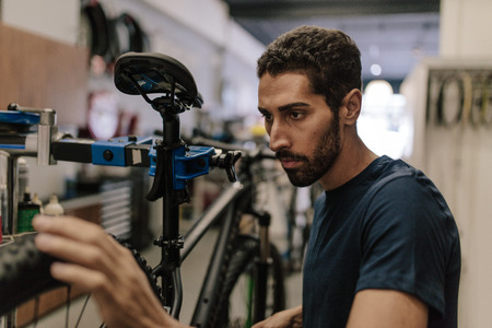 Worker repairing a bicycle at workshop. Man aligning the wheel of a bicycle in a repair shop.