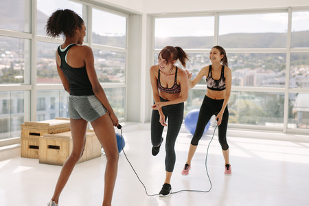 Three diverse girls jumping rope and having fun in studio. Two women rotating the rope with one woman jumping and smiling at fitness studio.