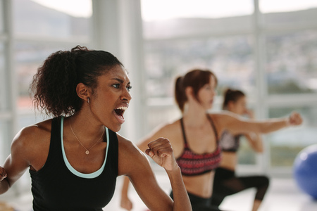 Group of women in gym class doing punching exercise. African woman shouting during workout at fitness class.