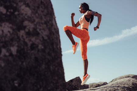 Sports woman doing jumping and stretching workout outdoors. Full length of healthy young african fitness woman doing exercise at rocky beach. Stock Photo