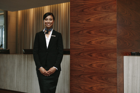 Portrait of happy young female receptionist standing at hotel front desk to welcome guest. Female concierge welcoming guest in hotel. Фото со стока