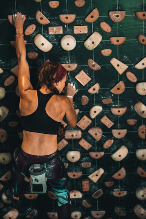 Woman climbing wall at an indoor wall climbing centre. Rock climber practicing climbing at an indoor climbing gym. Stock Photo