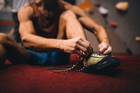 Cropped shot of man sitting on the floor and wearing griping shoes for wall climbing. Man tying shoe laces at a gym.