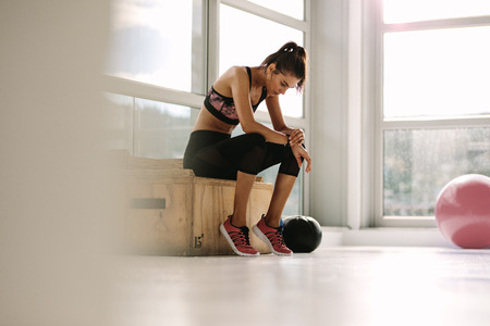 Young woman resting on box after workout at gym. Fitness female taking break after training session in health club.
