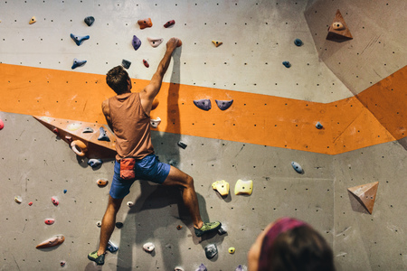 Man bouldering at an indoor climbing centre while a woman looks on. Climber practicing rock climbing at an indoor climbing gym.