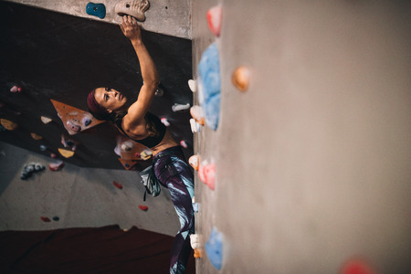 Athletic woman bouldering at an indoor climbing centre. Woman climber trying to reach for the grips while climbing at an indoor climbing gym.