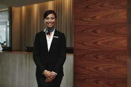 Portrait of happy female hotel receptionist standing at workplace. Smiling woman receptionist working in hotel.