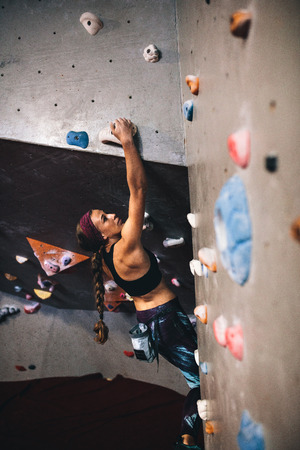 Woman bouldering at an indoor climbing centre. Climber practicing rock climbing at an indoor climbing gym.