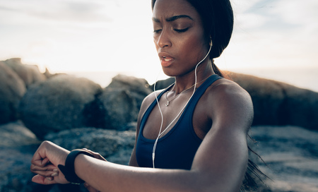Close up of young fitness woman looking at her smart watch while taking a break from outdoor workout. Sportswoman checking pulse on fitness smart watch device.