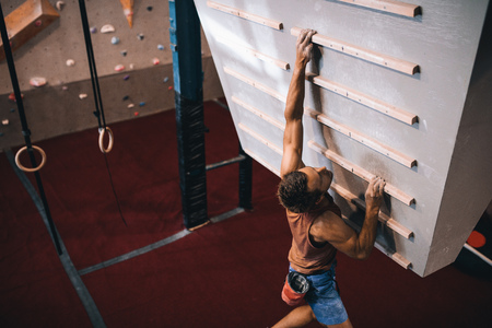 Man practicing wall climbing on a campus board. Man climbing on a campus board at a wall climbing gym. Stock Photo - 97405963
