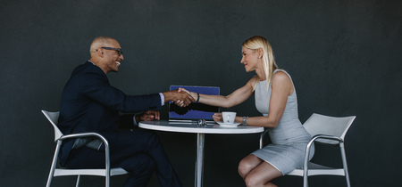 Two business people shaking hands after a successful meeting. Businessman and woman hand shake at cafe over a deal.