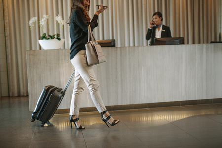 Business woman walking in front of hotel reception with luggage and having a phone call. Female guest arriving in hotel with suitcase. Stockfoto