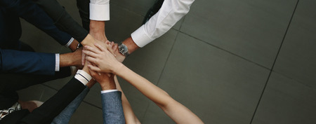 Overhead view of business team putting hands together at the office. Office workers making a stack of hands with copy space.