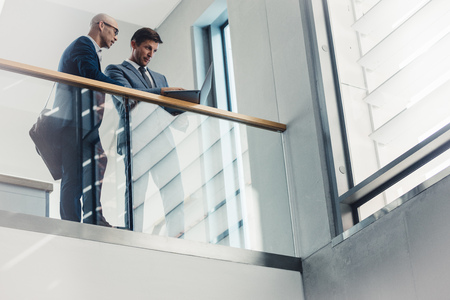 Low angle view of two businessmen looking at laptop while standing by a railing. Business people working together in office. Banco de Imagens