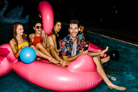 Group of men and women having fun and laughing on an inflatable flamingo pool float mattress. Cheerful friends hanging out in a pool in evening. Evening pool party. 版權商用圖片 - 97319366