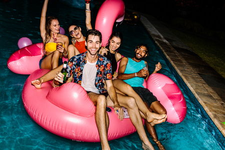 Portrait of happy men and women sitting together on an inflatable pool float. Friends hanging out at evening pool party. 版權商用圖片 - 97319677