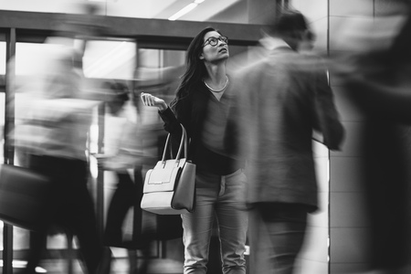 Asian businesswoman waiting for someone with people rushing in the lobby. Motion blur effect. Black and white shot. Stockfoto