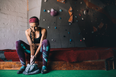 Woman at a wall climbing gym applying magnesium chalk powder on hands from a bag. Artificial bouldering wall in the background. Stock Photo