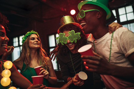 Group of young men and woman celebrating St. Patrick's Day. Friends having fun at the bar with green party glasses and hat.
