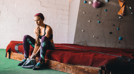 Woman at a wall climbing gym applying magnesium chalk powder on hands from a bag. Artificial bouldering wall in the background. Фото со стока