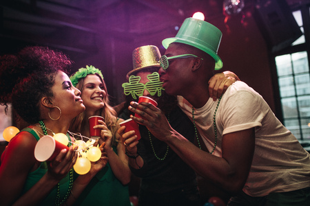 Multi-ethnic men and women having fun at the bar. Group of friends celebrating St. Patrick's Day at nightclub.