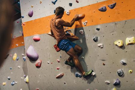 Man bouldering at an indoor climbing centre. Climber practicing rock climbing at an indoor climbing gym.