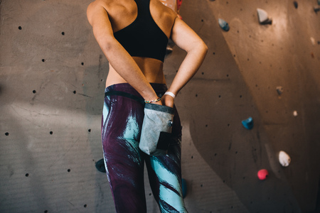 Rear view of woman at applying magnesium chalk powder on hands from a bag tied to her waist. Cropped shot of woman applying gripping powder before climbing boulder wall at a wall climbing gym.