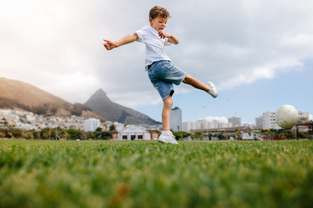 Boy kicking a football in a playground. Low angle view of a boy playing football in a playfield.