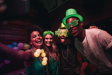 Group of friends enjoying at party in the bar and taking selfie with smart phone. Cheerful en and women partying and celebrating St.Patricks Day at night club. Stock Photo