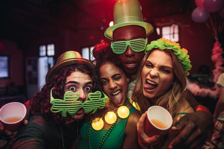 Crazy young friends enjoying a party at pub. Men and women in green clover party glasses and leprechaun hat at night club. People celebrating St.Patricks day. Stock fotó