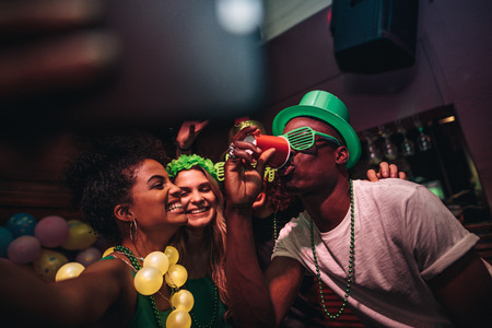 Man drinking a glass of beer with female friends smiling and taking selfie at bar. Young people celebrating St.Patricks day at night club and taking selfie with phone.