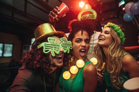 Group of young friends celebrating St. Patricks Day at bar. People having fun at the bar.