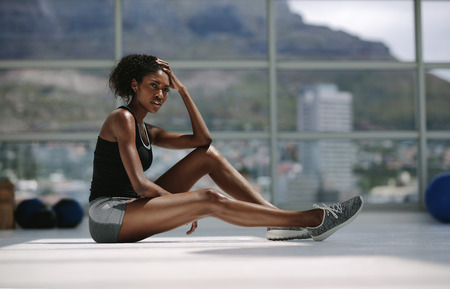 Young female sitting relaxed after workout at health club. Woman resting after intense training at fitness studio.