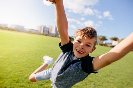 Close up of a boy jumping in air at a park. Cheerful boy enjoys being lifted in air while playing in a park.