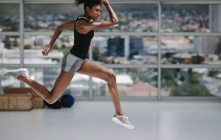 Female with slim figure running and jumping in fitness studio. Healthy african woman working out indoors.