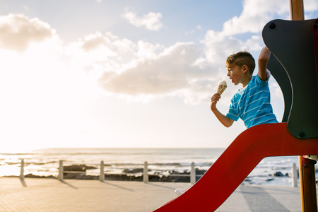 Boy eating an ice cream sitting on a slide at the seafront on a sunny evening. Little boy on vacation treating himself to an ice cream.