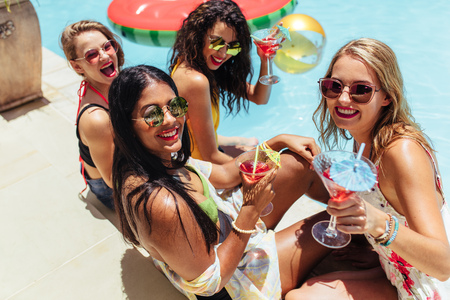 Happy multiethnic female friends with drinks having pool party during vacation at resort. Group of women hanging out by the swimming pool and having cocktails on summer day.