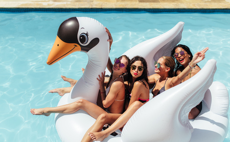 Group of friends on vacation sitting together on an inflatable swan in swimming pool. Multi-ethnic women friends enjoying on a inflatable white swan in pool. Stockfoto