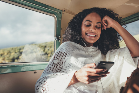 African woman on road trip travelling by van. Smiling female sitting on backseat of car and  listening music with mobile phone.