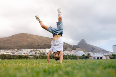 Boy balancing on hands in upside down position in a ground. Boy playing acrobatically in a ground.