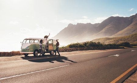 Female friends enjoying on a road trip. Group of women travelling in old minivan. Friends having fun outdoors on countryside road. Stock Photo