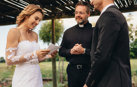 Woman read vows from paper for her husband at wedding ceremony background. Female partner reading marriage vows in ceremony with priest standing by.