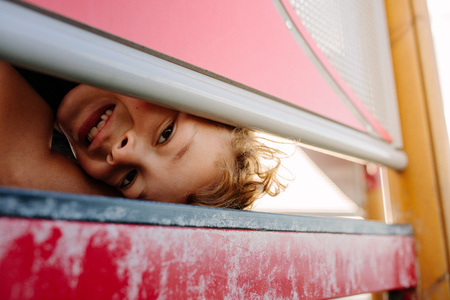 Close up of a boy looking through an opening of a signage frame. Boy on vacation in a playful mood. Banco de Imagens