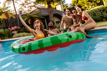 Multi-racial group of friends having fun in a swimming pool and taking selfie. Cheerful young friends with drinks taking selfie by the pool.
