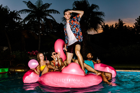 Man standing on inflatable mattress and looking forward with friends sitting at back. Group of men and women partying in the pool at night.