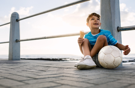 Boy sitting near a seashore railing with an ice cream in hand and a football by his side. Little boy on vacation treating himself to an ice cream. Foto de archivo