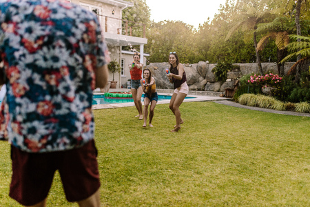 Three women with water guns in hand running towards a male friend outdoors. Friends playing with water guns outdoors. Stock Photo