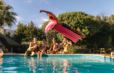 Man jumping in the swimming pool with inflatable mattress and friends sitting on the edge of the pool. Friends enjoying a summer day at pool side.