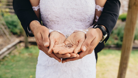 Close up of bride and groom putting their hands together and holding wedding rings on their palms. Close up of two wedding rings on newly married couples hands.